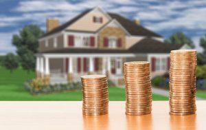 家が背景にある積まれたコイン