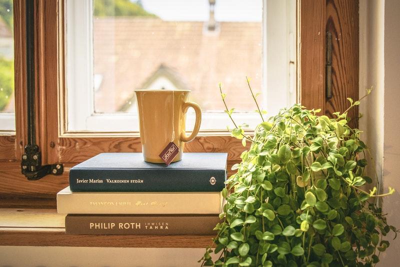 木製サッシの窓のそばにあるコーヒーと本