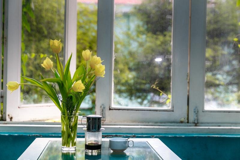 窓辺にあるコーヒーと花